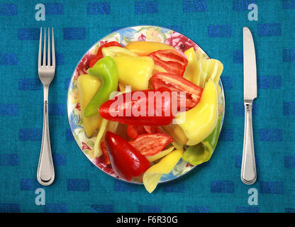 bell peppers on plate, knife and fork on table - Stockfoto