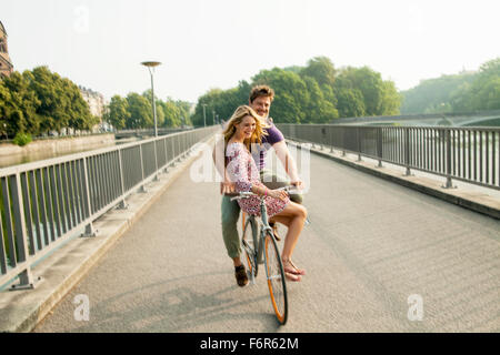 Young couple riding bicycle on city bridge - Stock Photo