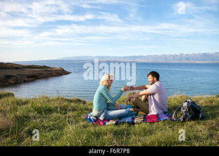 Young couple having a picnic on water's edge - Stock Photo
