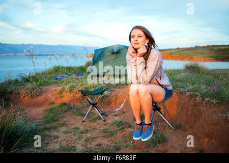 Young woman at campsite day dreaming - Stock Photo