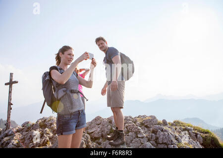Group of friends taking pictures in mountain landscape - Stock Photo
