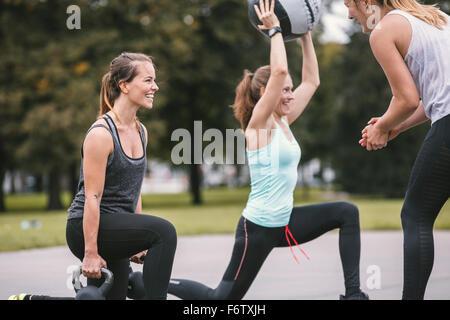 Three women having an outdoor boot camp workout - Stock Photo