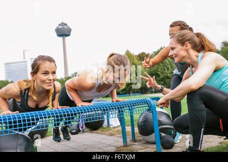 Four women having an outdoor boot camp workout - Stock Photo