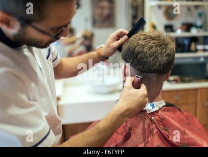 Barber shaving head of a customer - Stock Photo