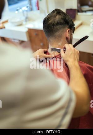 Barber shaving neck of a customer - Stock Photo