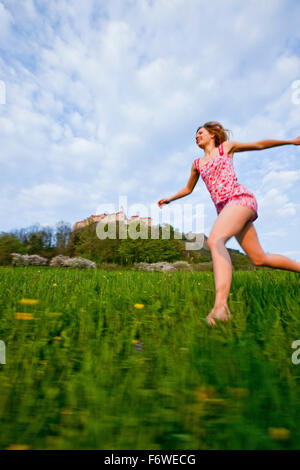 Young woman running over a meadow, Riegersburg castle in background, Styria, Austria - Stock Photo