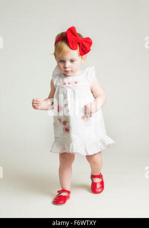 A cute little one year old girl learning to walk in red shoes and bow - Stock Photo