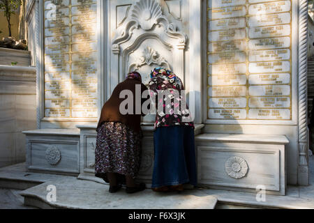 Moslem women draw water at a fountain outside Eyup Mosque in Istanbul, Turkey - Stock Photo