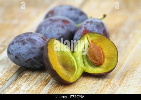 Fresh plums on rustic wooden surface, closeup - Stockfoto