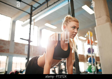 Indoor shot of young fitness woman doing push ups in gym. Caucasian female working out in health club. - Stock Photo