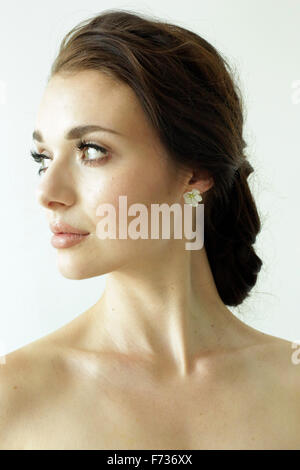 Portrait of a woman with brown hair tied in an elegant bun. - Stock Photo