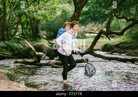 A woman giving a boy a piggyback and holding a shrimping net wading in a shallow stream. - Stock Photo