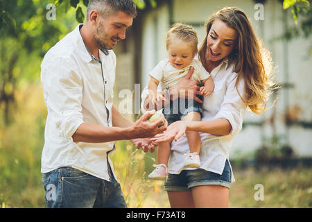 Families with a child in the summer garden - Stock Photo