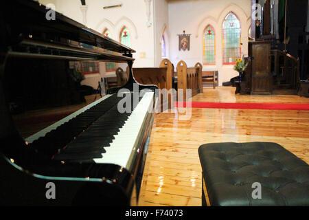 Close up shot of a beautiful black grand piano in a church - Stock Photo