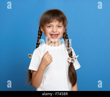 happy lost tooth girl portrait, studio shoot on blue background - Stock Photo