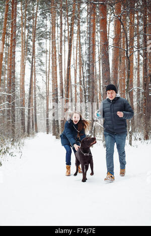 Young Couple with a Dog Having Fun in Winter Forest on Vacations. Selective Focus. Lifestyle of Happy Modern Family. - Stock Photo