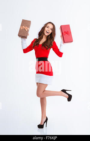 Full length portrait of a cheerful woman in santa claus cloth holding gift boxes isolated on a white background - Stock Photo