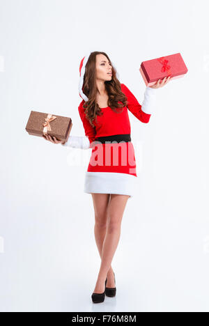 Full length portrait of a thoughtful woman in santa claus cloth holding two gift boxes isolated on a white background - Stock Photo