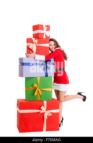 Full length portrit of a happy woman in santa claus cloth hugging many gift boxes isolated on a white background - Stock Photo