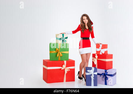 Full length portrait of a happy woman standing with many present boxes isolated on a white background - Stock Photo