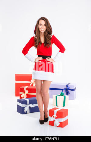 Full length portrait of a smiling woman standing with many present boxes isolated on a white background - Stock Photo
