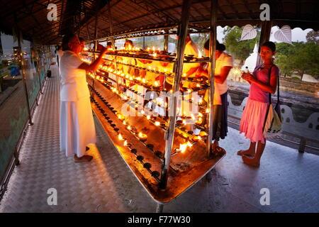 Sri Lanka, Kandy -  pilgrims light up candles in the Temple of the Tooth, Sri Dalada Maligawa, UNESCO World Heritage - Stock Photo
