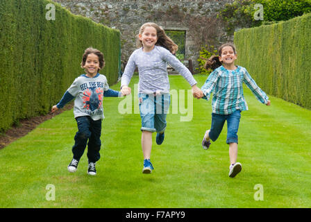 Three children running along the grass at the Rose Gardens at Drum Castle in Aberdeenshire, Scotland. - Stockfoto