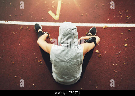 Back view of young woman in sportswear sitting on track field and preparing before training.Unrecognizable - Stockfoto