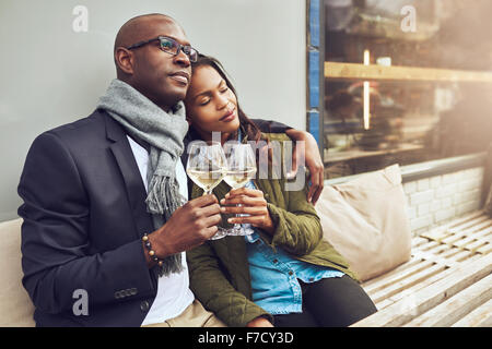 Romantic loving couple enjoying each others company sitting relaxing on a wooden restaurant bench in a close embrace - Stockfoto