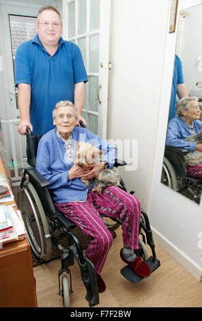 Male carer pushing an elderly woman in a wheelchair (could be mother & son) - Stockfoto