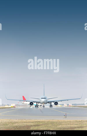 Passenger jet planes are taxiing to the runway for a takeoff - Stock Photo