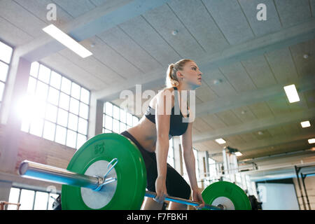 Determined young fitness woman training with heavy weights. Caucasian female athlete doing weight lifting workout - Stock Photo