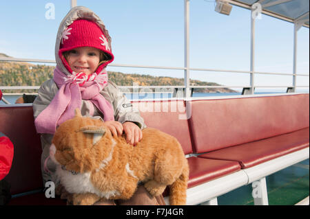 Little girl sitting on ferry boat with stuffed cat on her lap, portrait - Stock Photo