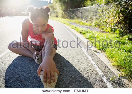 High school athlete stretching leg on running track - Stock Photo