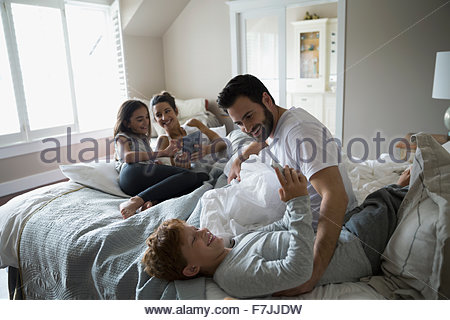 Family relaxing with digital tablets in bed - Stock Photo