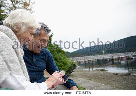 Senior couple using cell phone at lakeside - Stock Photo