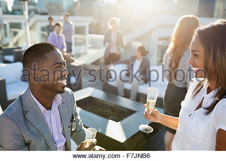 Smiling business people drinking champagne on sunny rooftop - Stock Photo