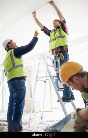 Construction worker on ladder at construction site - Stock Photo