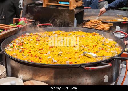 Paella rice dish in large cooking pan at market - Stock Photo