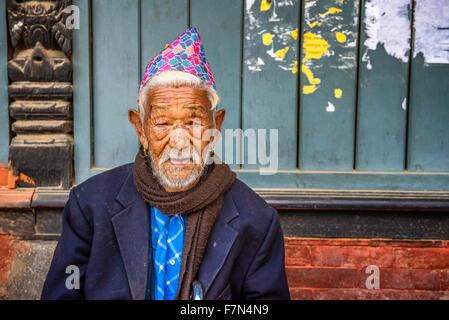 Elderly man sitting in the street of Kathmandu - Stock Photo