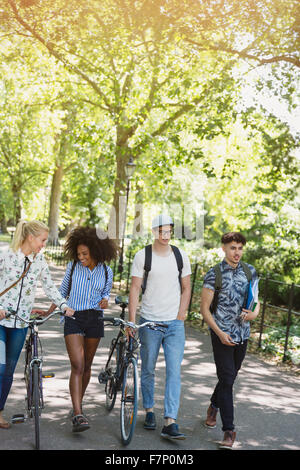 Friends walking with bicycles in park - Stock Photo