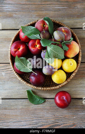 sweet ripe plums on wicker plate, fruit top view - Stock Photo