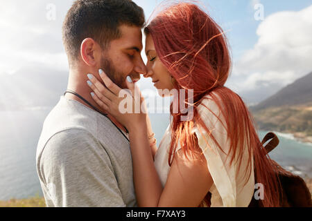 Portrait of affectionate young couple about to kiss. Romantic young man and woman sharing a lovely moment on their - Stock Photo