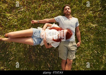 Young man and woman lying on the lawn sleeping. Overhead view of young couple resting together on the grass. - Stock Photo