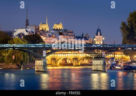 Pont des Arts, Pont Neuf, Notre Dame de Paris Cathedral towers and Seine River. Illuminated evening view. Ile de - Stock Photo