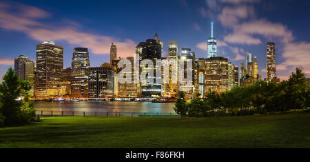Evening view of Lower Manhattan illuminated skyscrapers across Brooklyn Bridge Park. Manhattan Financial District, - Stock Photo