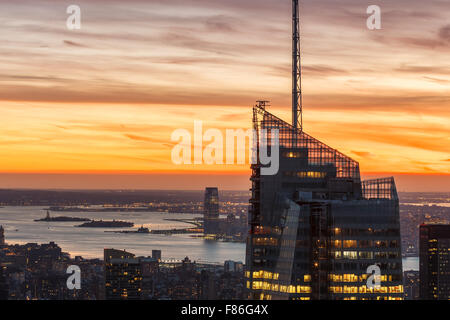 Aerial view of Midtown Manhattan and Bank of America Tower at sunset. The Statue of Liberty appears in New York - Stock Photo