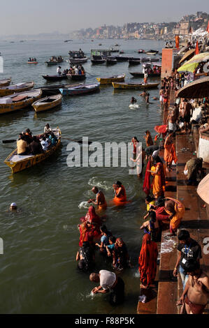 Hindu devotees praying in knee deep ganga water at Ghat in Varanasi. Varanasi is the second oldest city in the world, - Stock Photo