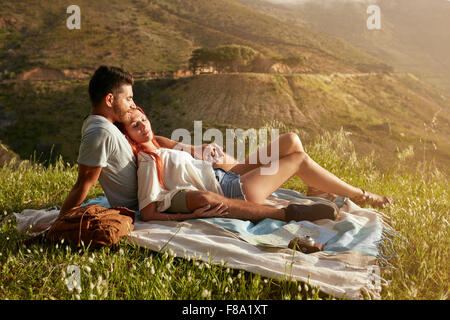 Young couple having picnic on a meadow on a bright sunny day. Caucasian man and woman relaxing at picnic on a summer - Stock Photo
