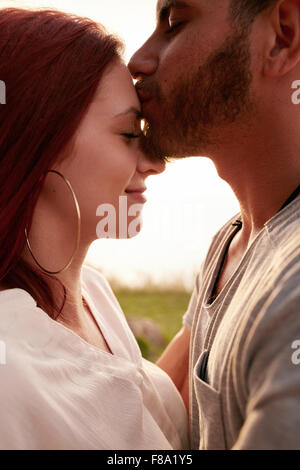 Portrait of loving young couple together outdoors. Young man kissing forehead of his girlfriend. - Stock Photo